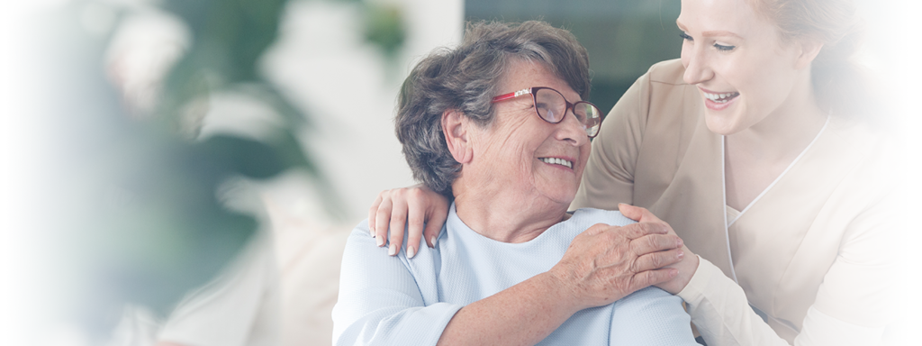 cosinuss-elderly-care_happy-patient-is-holding-caregiver-for-a-hand-while-spending-time-together_688645165-1024x384